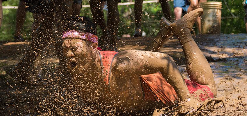 Student diving in mud at Oozeball