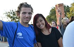 A female and male international student smiling outside