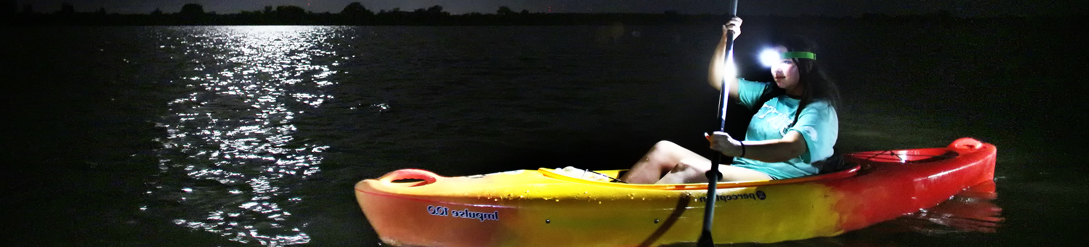 Student on a moon light paddle in a canoe